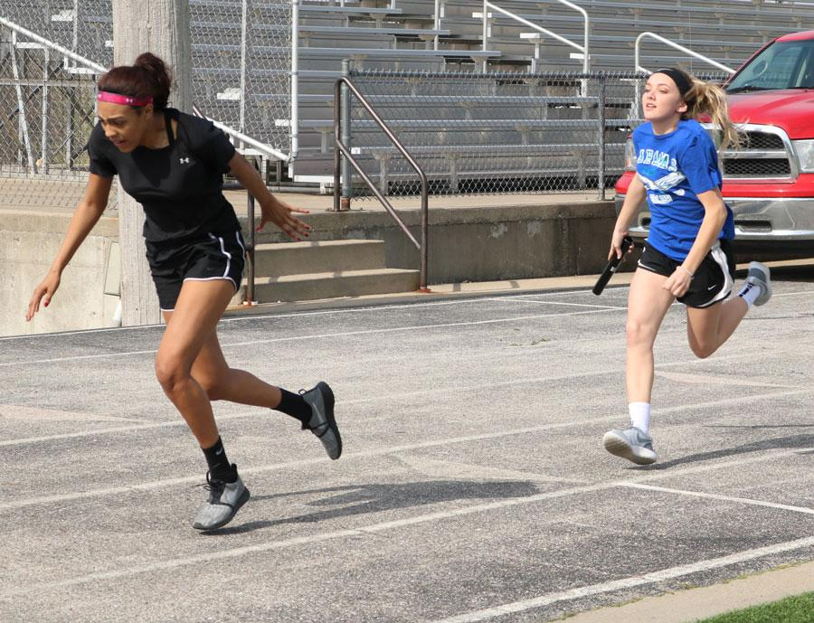 Freshman Rayni Simons passes the baton to freshman Ariaunna Johnson. The track team started practice during the first week of March.