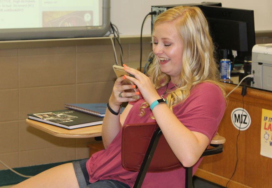 Senior Makalya Mais plays with her phone during staff retreat. Mais is the editor of The Wildcat and the Ozark Echoes yearbook.