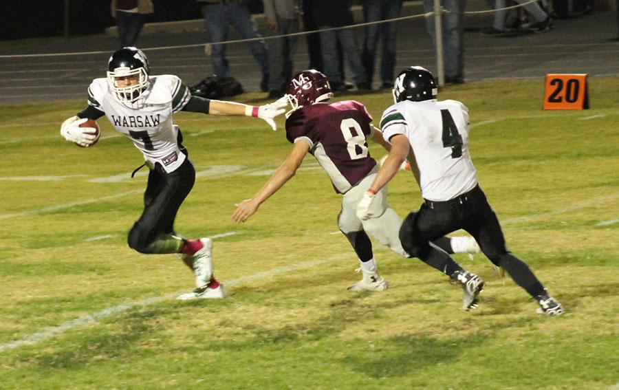 Senior Bailey Jelinek stiff-arms a Mt. Grove defensive player as junior Damian Adams attempts to protect the receiver.