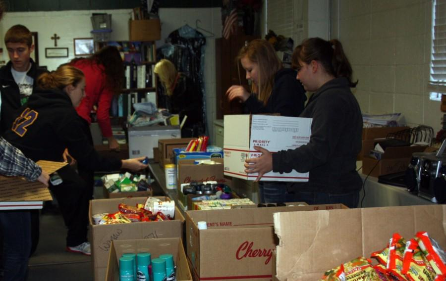 Junior Kylie McRoberts, Maddy McMillin and Mary Porter pack boxes for the soldiers overseas.