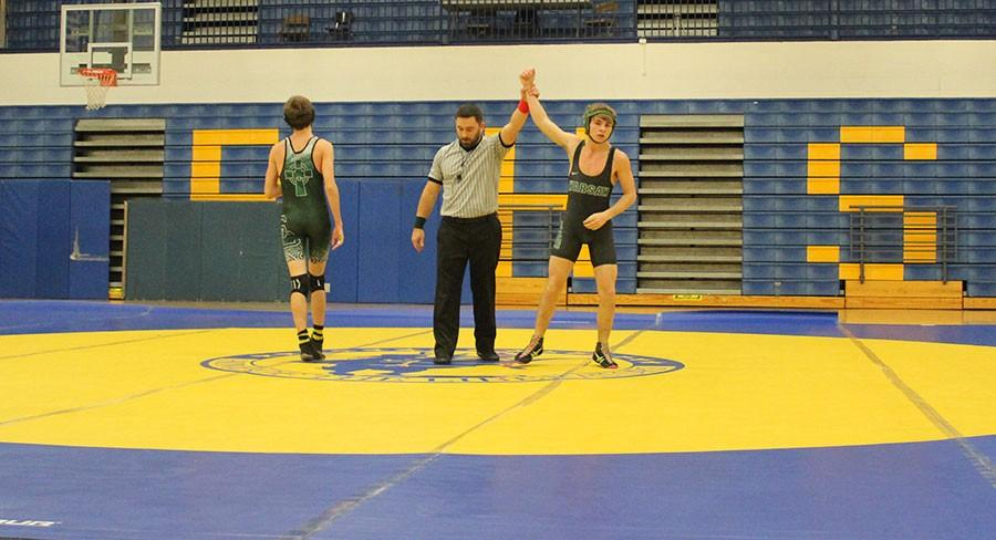 Senior Marshall Wilson get his hand raised after he won his match against Springfield Catholic. Wilson pinned his opponent.