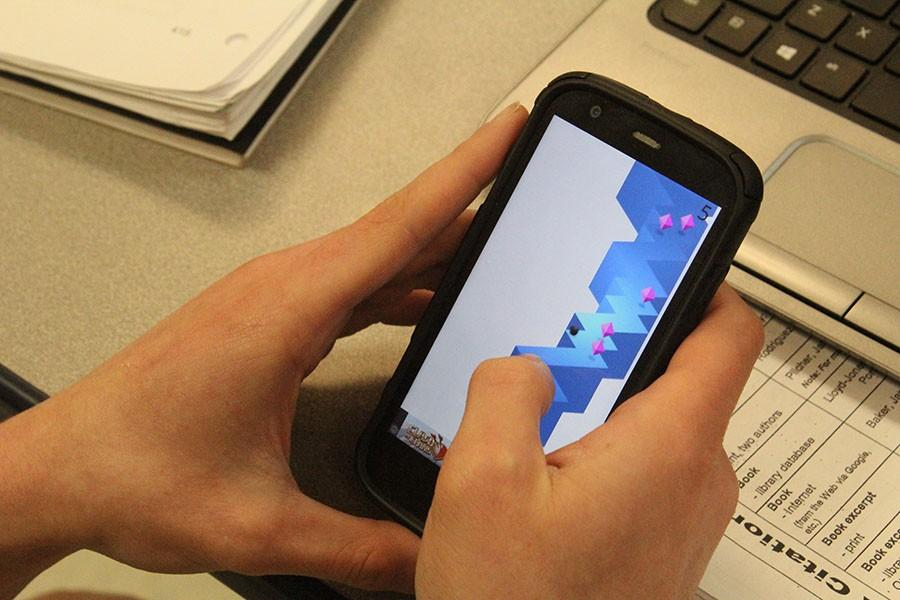 A student plays a game on their phone. Gaming is a large part of students lives.