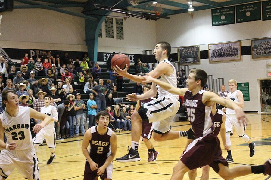Senior Joey Cooner takes the ball to the hoop in the Courtwarming game against Osage. Cooner made the game-winning free throw for the Cats' 81-80 victory.