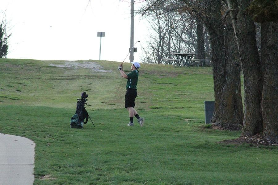 Senior Jake Freeman swings for the shot. The golf team was in a tournament.