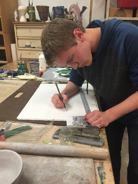 Junior Garrett Smith works on a drawing of his house for his drawing and painting class.