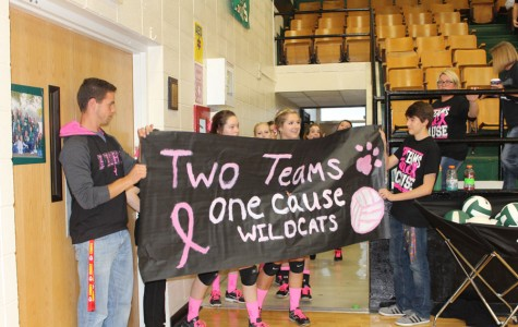 Senior John Hargrave and junior Tommy Reffett hold a banner that was made for the varsity volleyball team to run through. The team played their