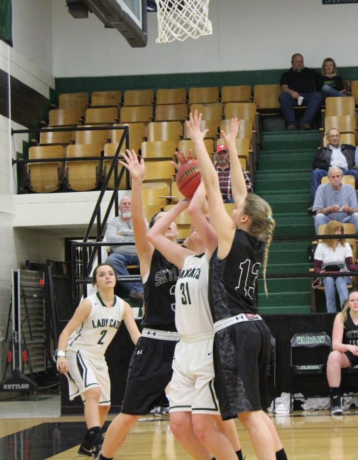 Junior Mackenzie Bauer tries to shoot a shot between two Skyline Tigers. The girls lost this game December 11th.
