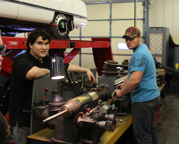 Juniors Dustin Coffee and Aaron Reno work in the automotive shop at State Fair's Career and Technical Center during the CTC visit day. They were displaying how to reform a brake rotor.