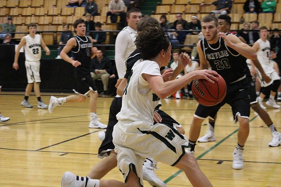 Freshman Logan Davis dribbles the ball down to set up a play during a game against Skyline. Davis started varsity this year.