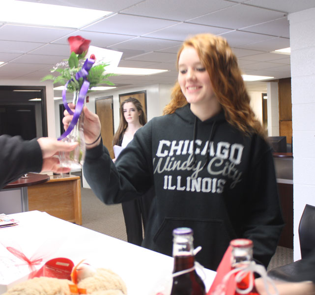 Junior Mackenzie Bauer receives her Valentine's gift in the office. Bauer, along with many other students collected flowers and candy on the last school day before Valentine's Day.