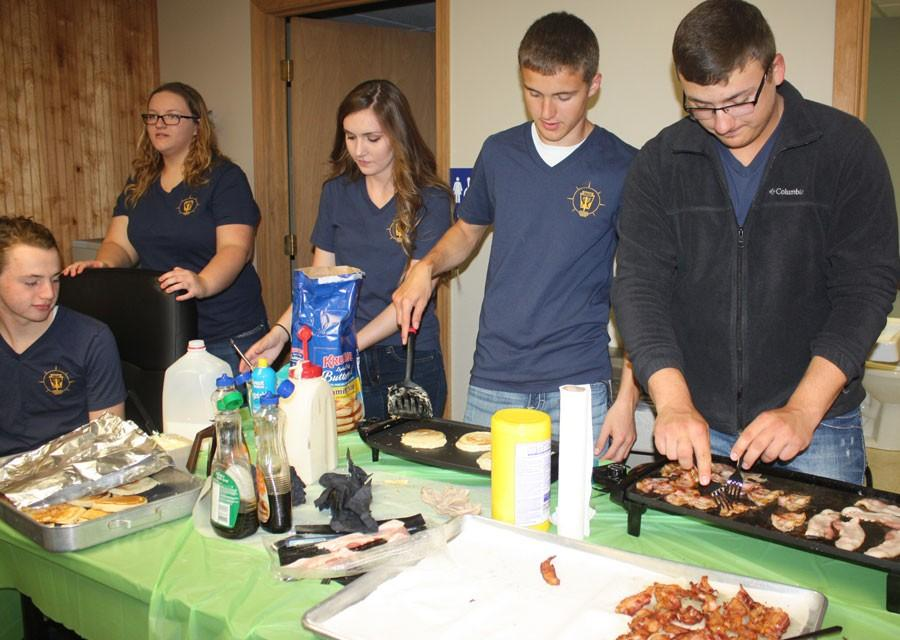 Junior Noah Long, Maddie Freeman, senior Bridget Clarke Michael Kephart and Austin McCall make pancakes and fry bacon for the teacher appreciation breakfast.