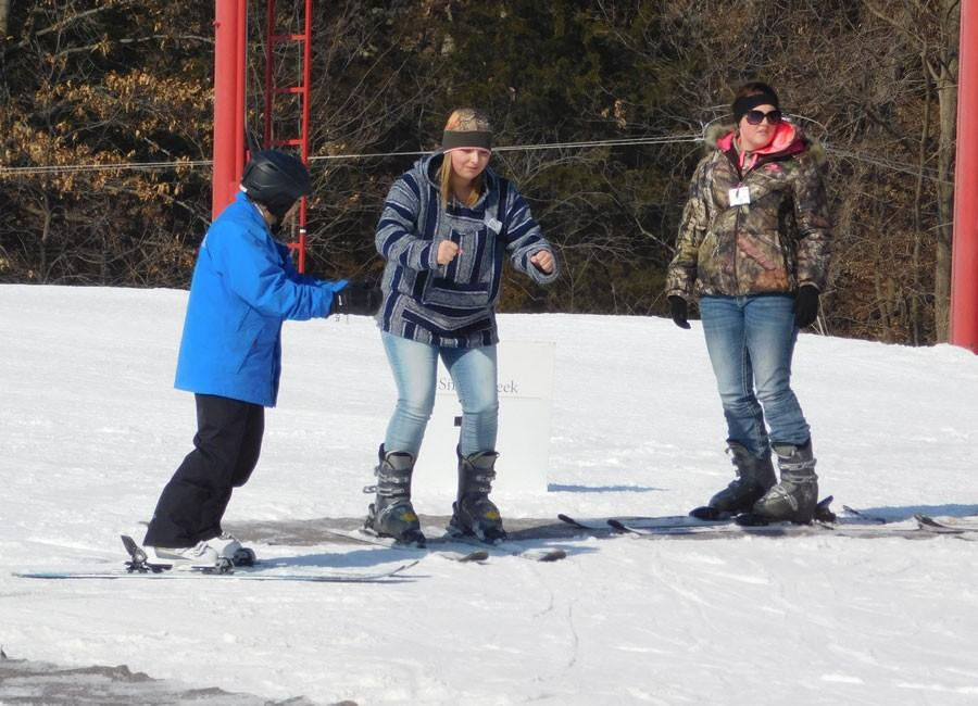 Senior Megan Barnett is instructed on how to hold her arms while sliding down the slope. FBLA members skied in Weston, MO at Snow Creek on Feb. 12.