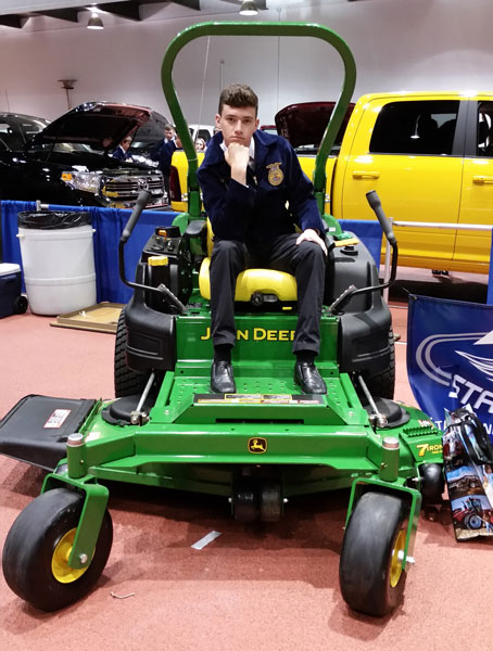 Senior Thane Henderson sits on a John Deere mower at the 2016 FFA State Convention career show.  This is Henderson's last year attending FFA State Convention as a student.