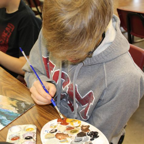 Senior Carter Phillips works on a painting in his art class.