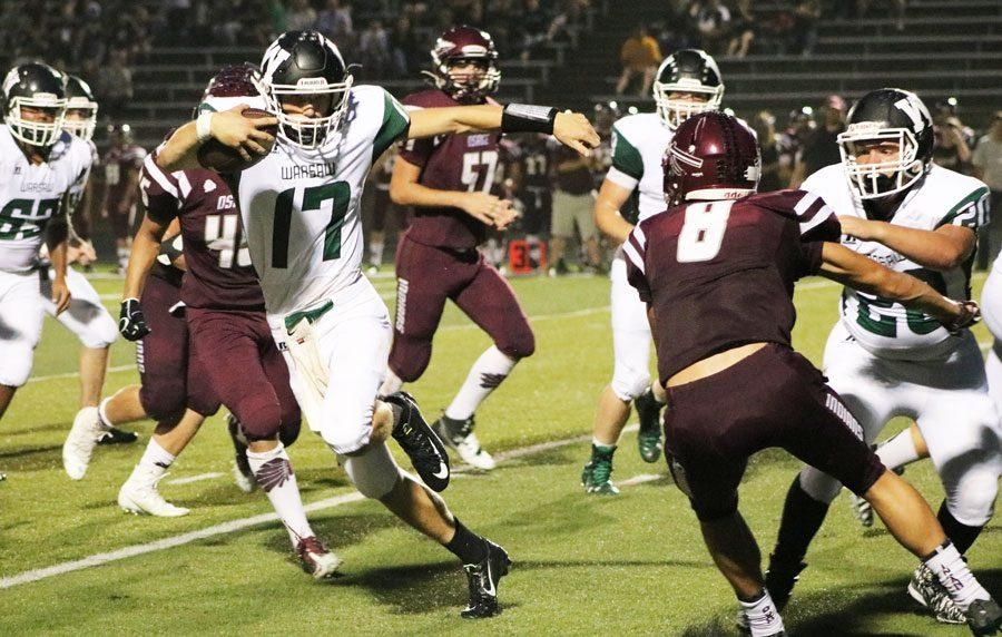 Sophomore quarterback Matt Luebbert runs the ball as sophomore offensive lineman Levi Lawson holds off an Osage defender. The Cats fell to the Indians 42-6 on Sept. 9.