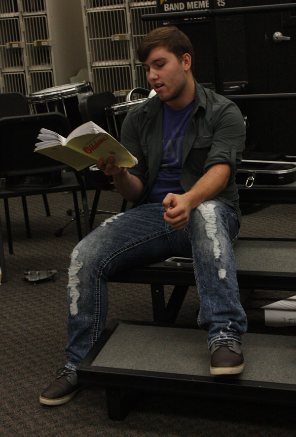 Junior Brenden Dockery reads through his lines while practicing with the Oklahoma pit orchestra. Dockery is portraying Curly in the musical.
