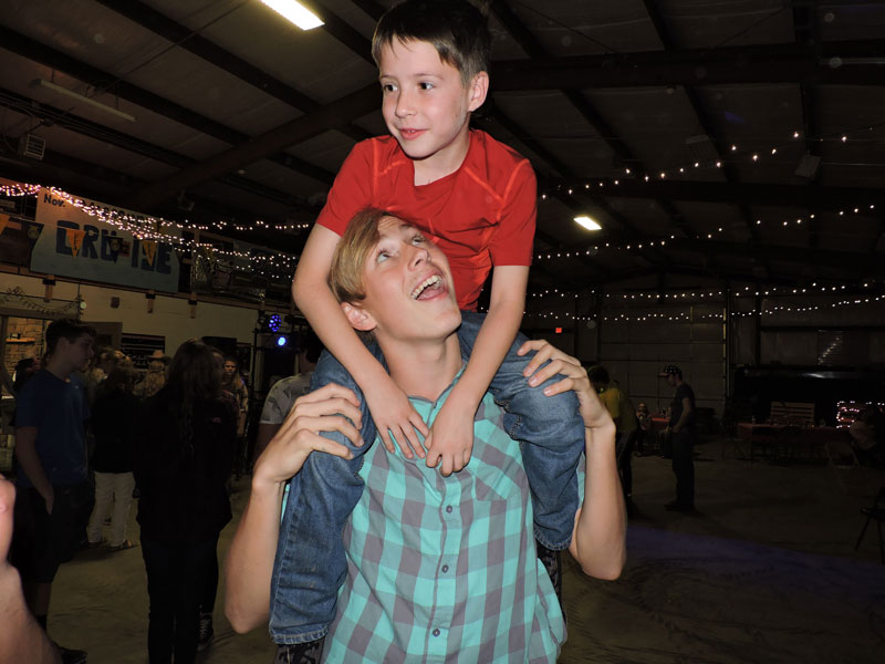 Sophomore+Tyler+Kirk+carries+Nate+Foster+on+his+shoulders+during+the+dance.+Barnwarming+was+held+in+the+AG+building%2C+and+guests+of+all+ages+could+attend.