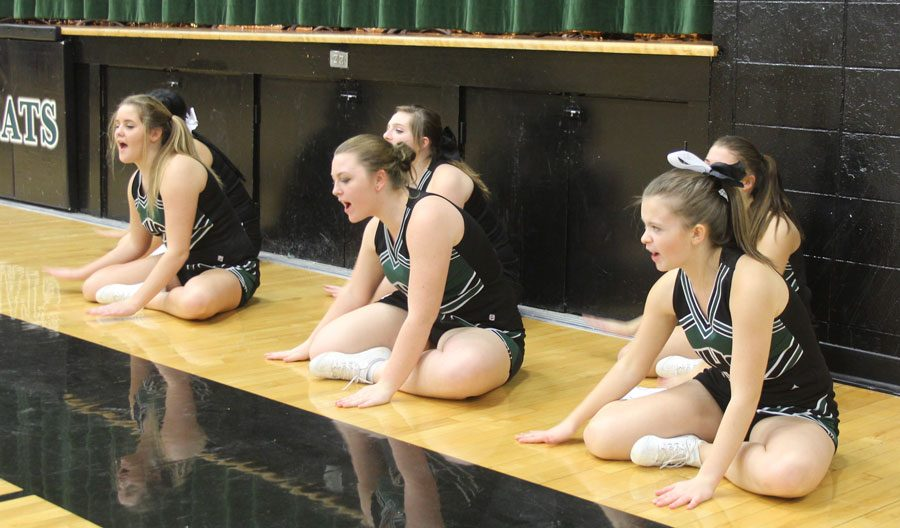 Freshman Maddie Breshears, junior Madi Rozzel, and junior Briar Heavener beat on the floor as part of one of their floor cheers. Floor cheers were newly added this year. Photo by Destiny Lee