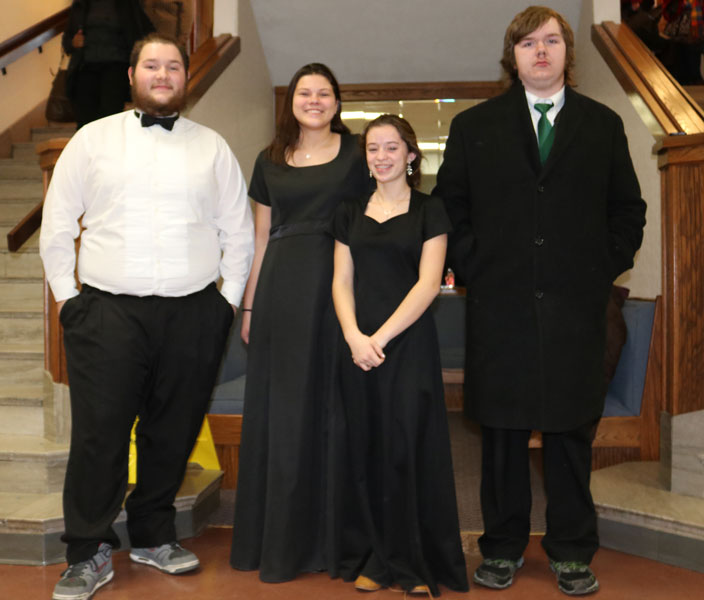 "Senior tubist Chris Bozarth, junior clarinetist Zoe Eledge, sophomore flutist Autumn Long, and senior euphoniumist Nathan Townley stand outside the concert hall. ""I believe everyone in band or choir should always try out for honor bands and things like it, you make so many memories that last a lifetime and they make you a better musician,"" Bozarth said."