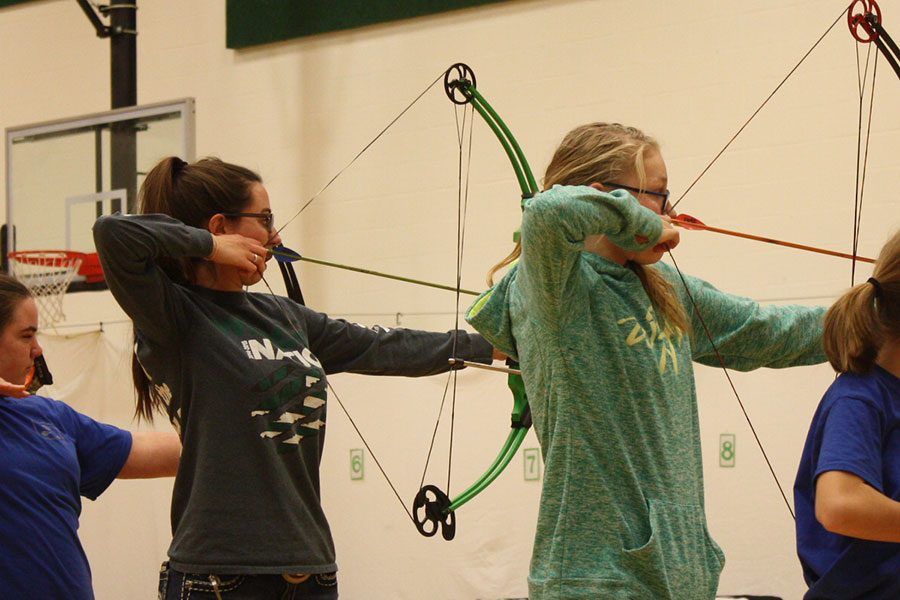 Senior Bailey Sharp and sophomore Caitlin Dueddenhoeffer shoot their bows during the archery tournament on Saturday, February 4.