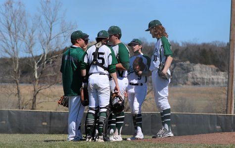 Coach Jerome Bagley talks to players including seniors catcher Hunter Bagley, pitcher Austin Gardner, second baseman Corey Callahan and junior first baseman Cash Miller during Saturday's game against Holden. This is Jerome's first year coaching for the school.