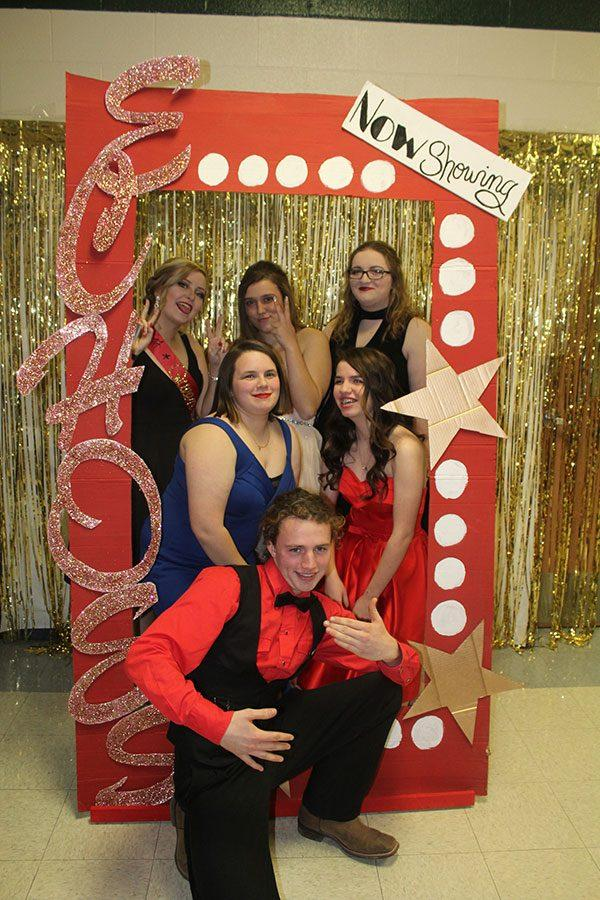 The yearbook staff takes a picture through the movie poster frame. The small staff enlisted help from the newspaper staff while decorating.
