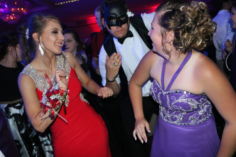 Seniors Ashlyn Yoder, Blake Brodersen, and Johna Newman dance together. Brodersen wore a batman mask to the masquerade.