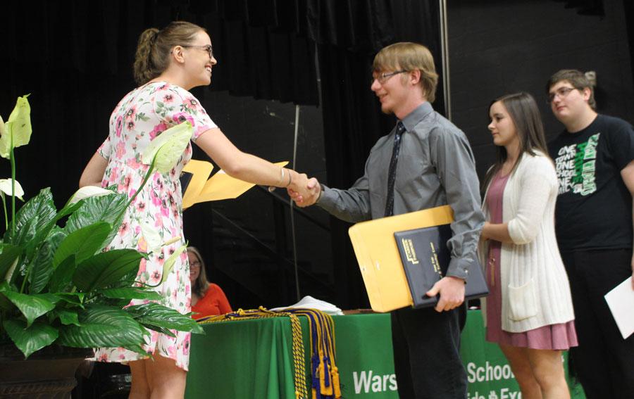 Senior Hunter Switzner receives awards from State Fair CTC representative Alexandra Richter. Switzner was in the graphic arts program.