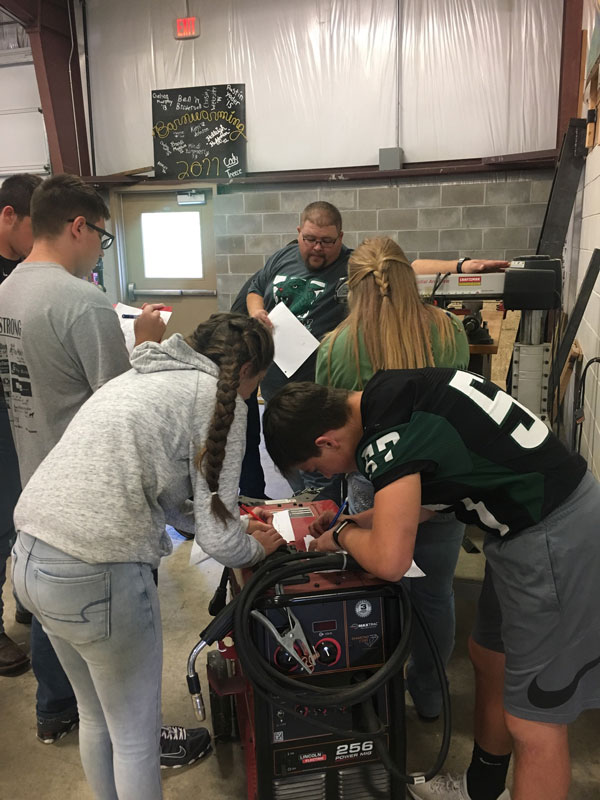Sophomores+Jacob+Weiser%2C+Allison+Pool%2C+Aidan+Comer+and+Savannah+Neth+take+notes+as+agriculture+teacher+Stan+Adler+demonstrates+the+parts+of+a+saw.+Students+did+shop+orientation+before+starting+shop+work.
