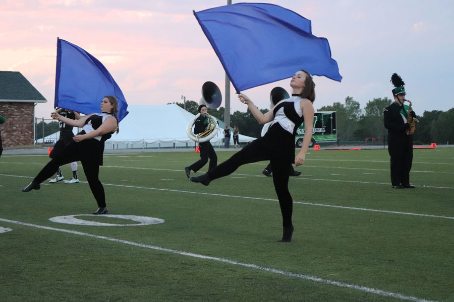 Freshman Sabrina Uptgraft and junior Ally Estes perform with swing flags.