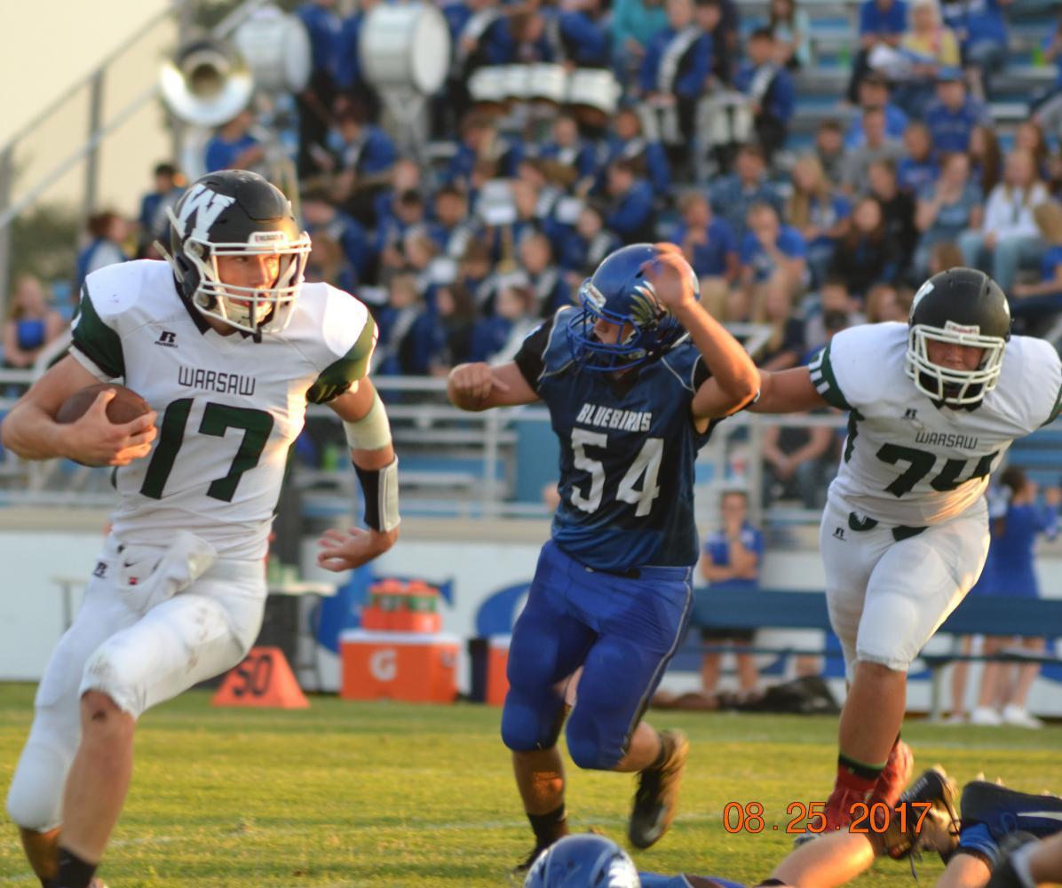 Junior quarterback Matt Luebbert runs the ball down the field. The football team beat Cole Camp 28-22. Photo by Kya Schepker.
