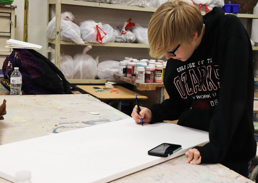 Senior Molly Baumhoff sketches on a canvas for her independent project in portfolio. Baumhoff has taken part in an art class since freshman year
