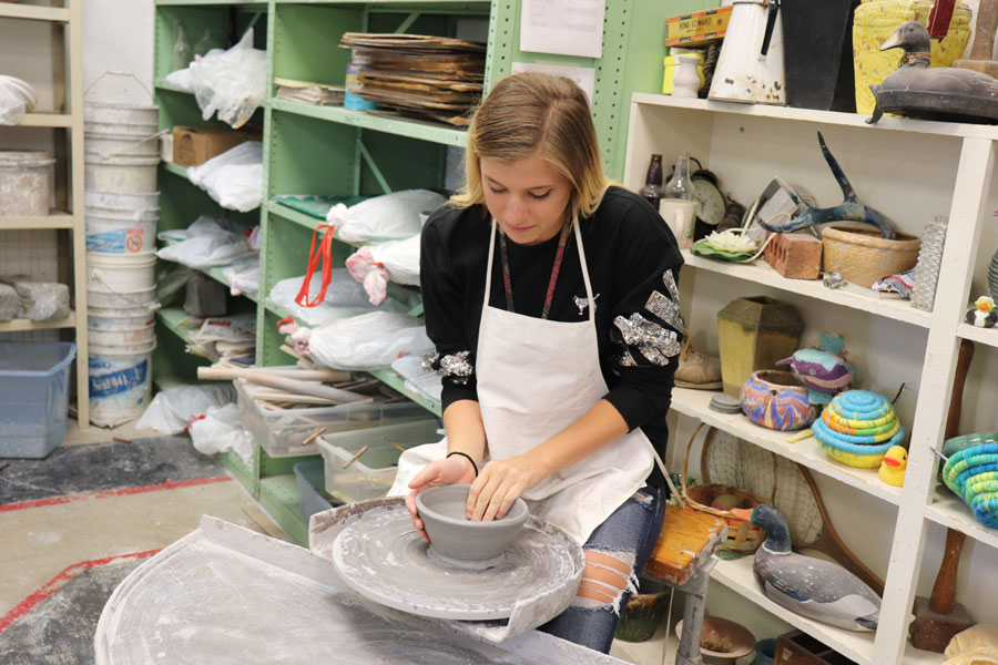 Senior Alexis Harris practices using the kick wheel to make a bowl in pottery. This was her first time on the wheel. Photo by Taylor Bunch.