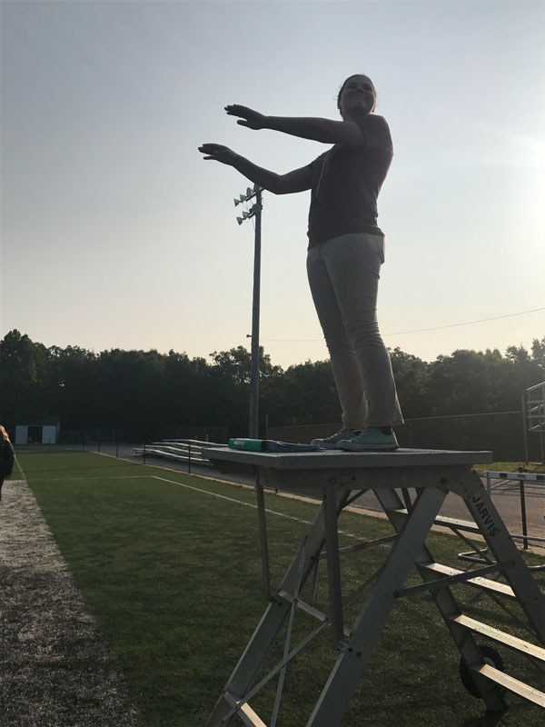 Drum Major Zoe Eledge conducts the marching band through their new routine during morning practice. The band got together every morning at 7 a.m. to run through sets and prepare for performances.