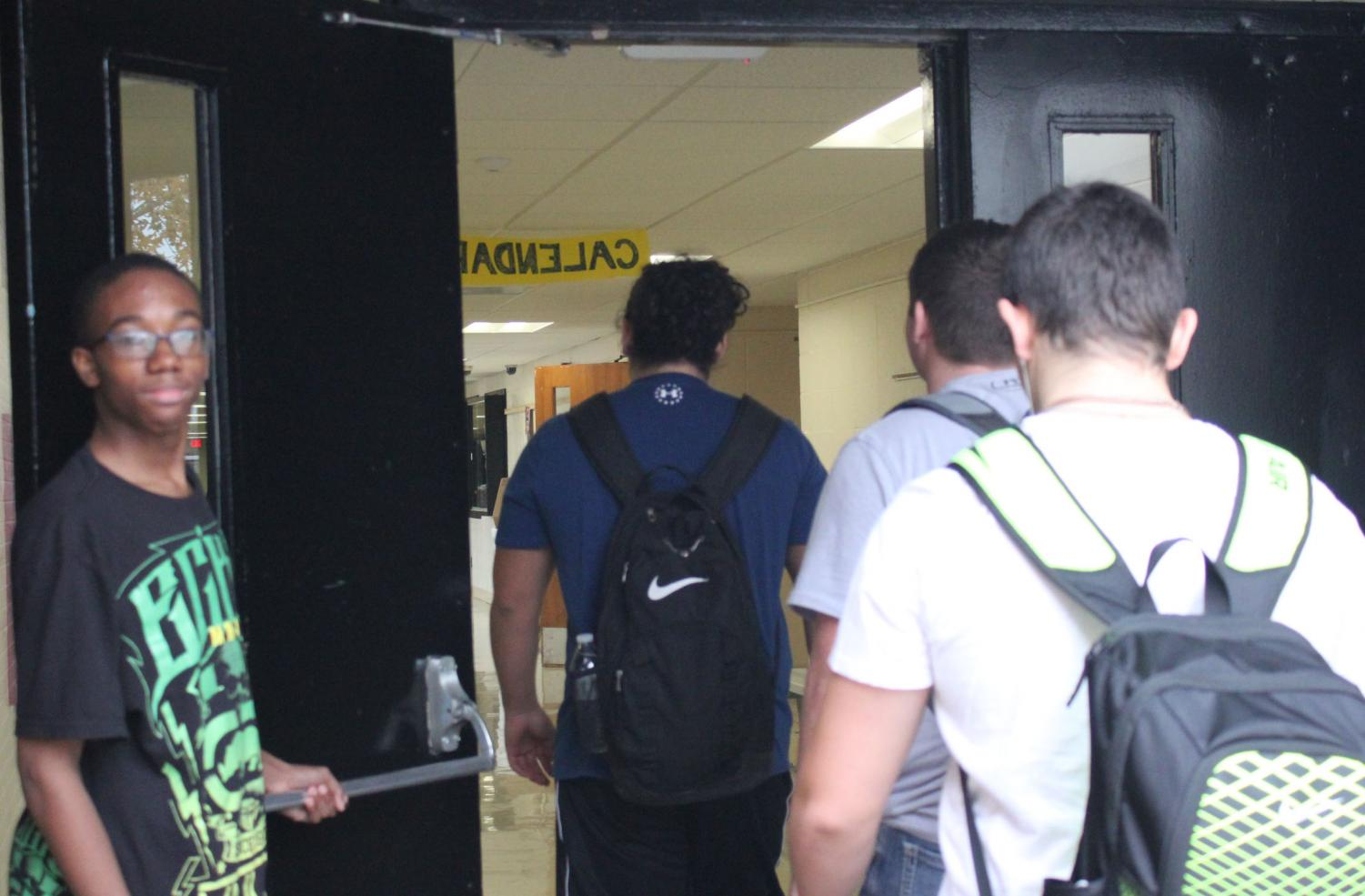 Freshman Ameer Evans holds the door open for students on their way to class. Evans makes this a recurrence everyday.