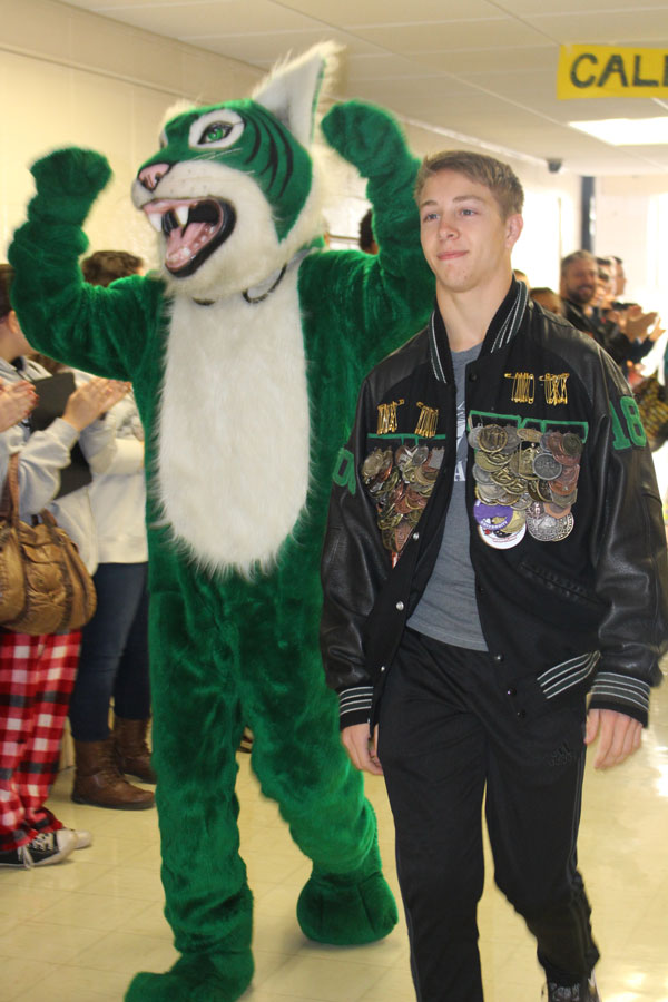 Senior Dallas Larsen walking the main hall through all of the Warsaw high school supporters. Larsen is having his state walk through the hall with the wildcat.