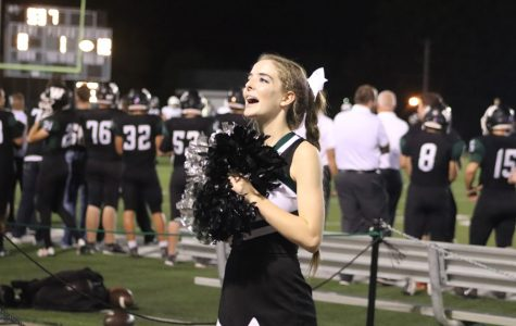 """Senior Hannah Chapman cheers at a home football game against Blair Oaks. Chapman participated in Cross country. volleyball, cheerleading and colorguard during the fall season. """"Dual sporting or triple sporting requires a lot of help from a lot of people. I wouldn't have been able to do it without my parents, coaches and my teammates,"""" Chapman said."""