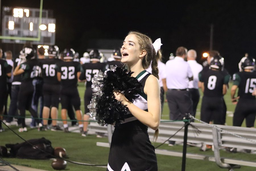 "Senior Hannah Chapman cheers at a home football game against Blair Oaks. Chapman participated in Cross country. volleyball, cheerleading and colorguard during the fall season. ""Dual sporting or triple sporting requires a lot of help from a lot of people. I wouldn't have been able to do it without my parents, coaches and my teammates,"" Chapman said."