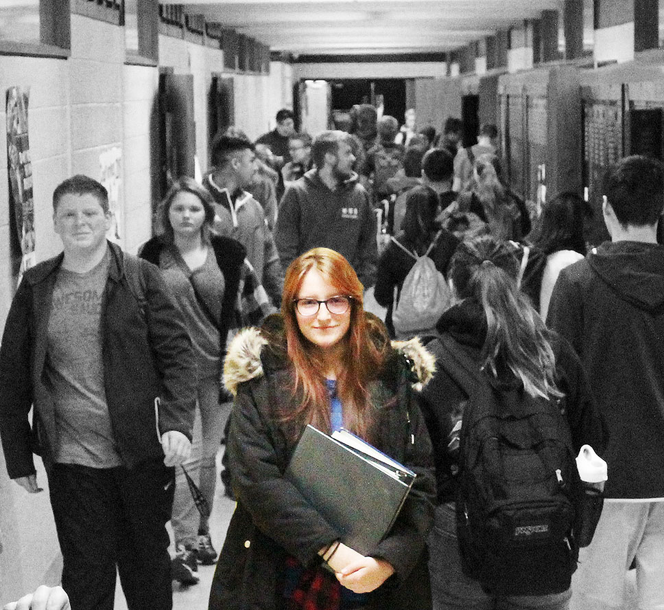 Sophomore Alexa Scrivener standing in hallway surrounded by fellow classmates