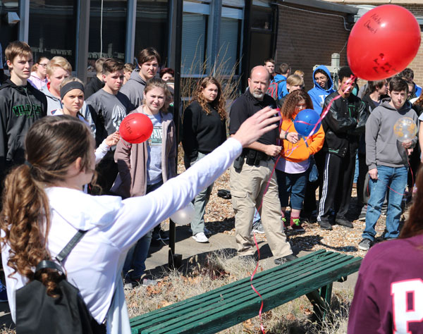 Senior Kyra Kleihauer releases one of the red balloons at the balloon release on March 14. Each red balloon had a name of a victim from the Parkland, Florida shooting.