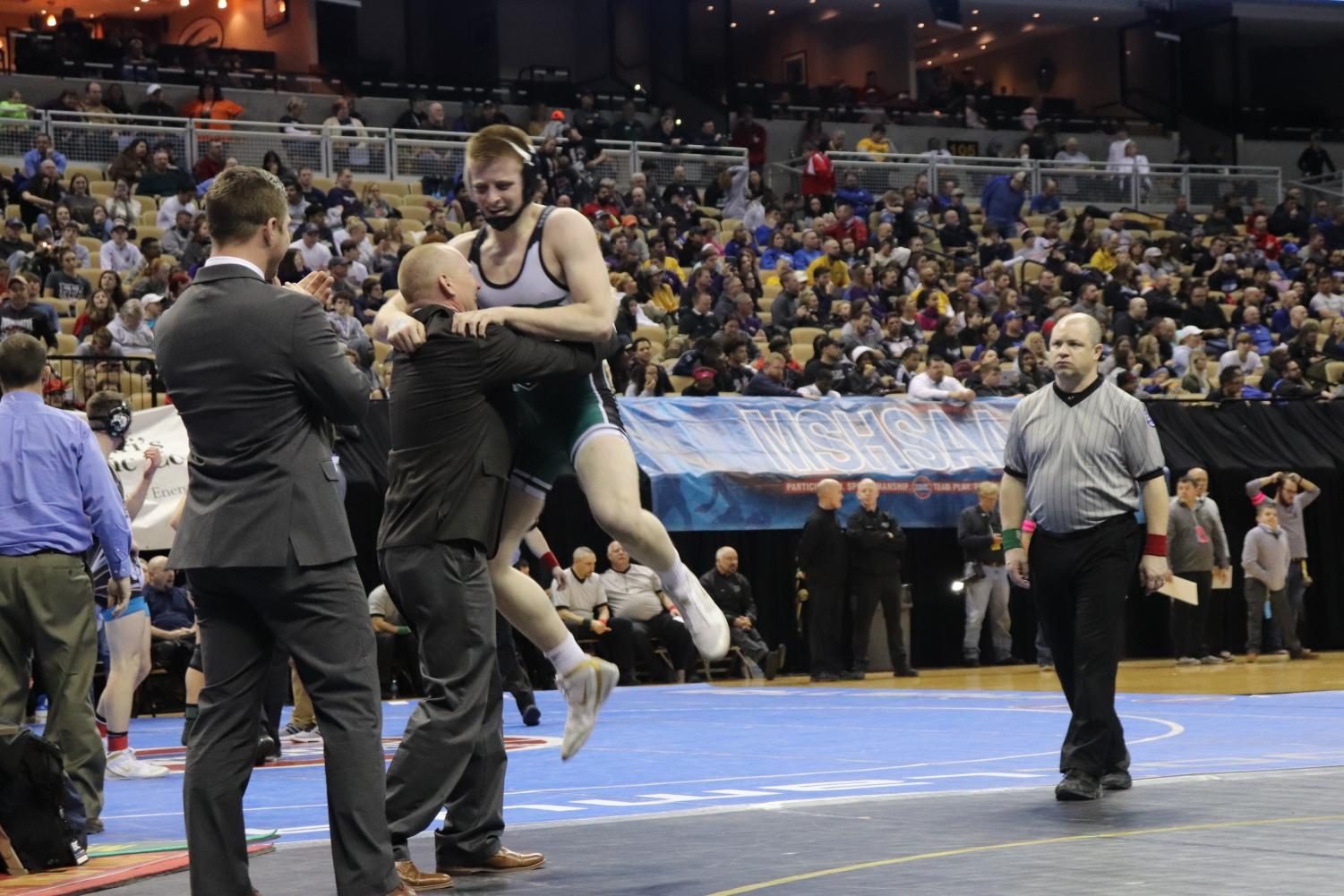 Senior Kolby Estes jumps into the arms of his father and coach after being declared the state champion in the class 152 weight class. Estes won second in state both his sophomore and junior years.