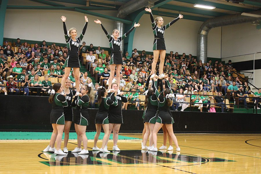 Flyers+junior+Hallie+Wenberg%2C+sophomore+Natalie+Johnson+and+junior+Darby+Mostaffa+wave+at+the+crowd+after+successfully+performing+a+stunt+at+the+Homecoming+assembly.