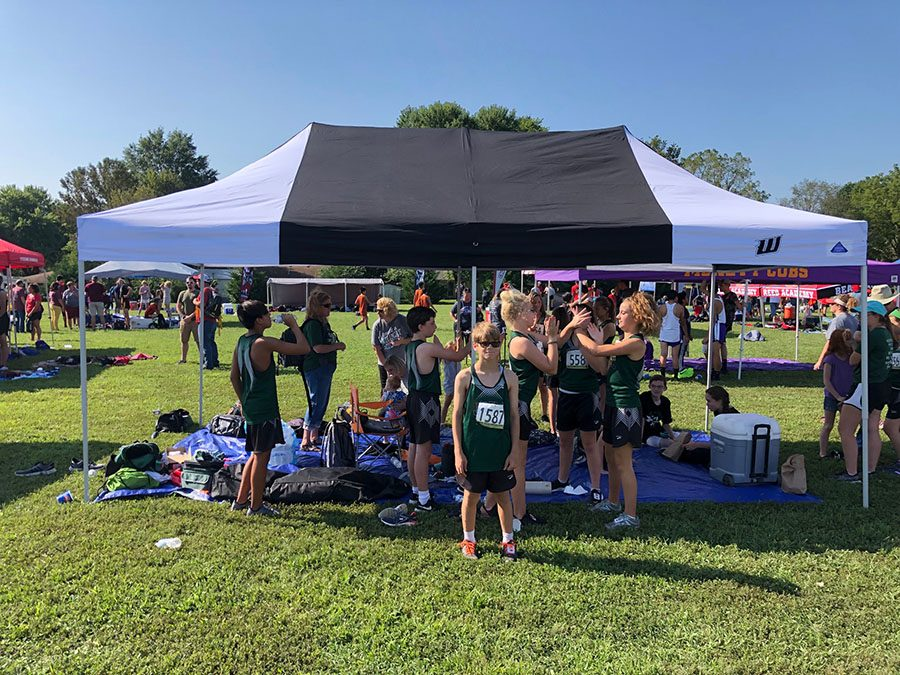 The middle school and high school cross country team enjoys their new tent at their Bolivar meet on Sept. 7.  Warsaw placed 15th overall.