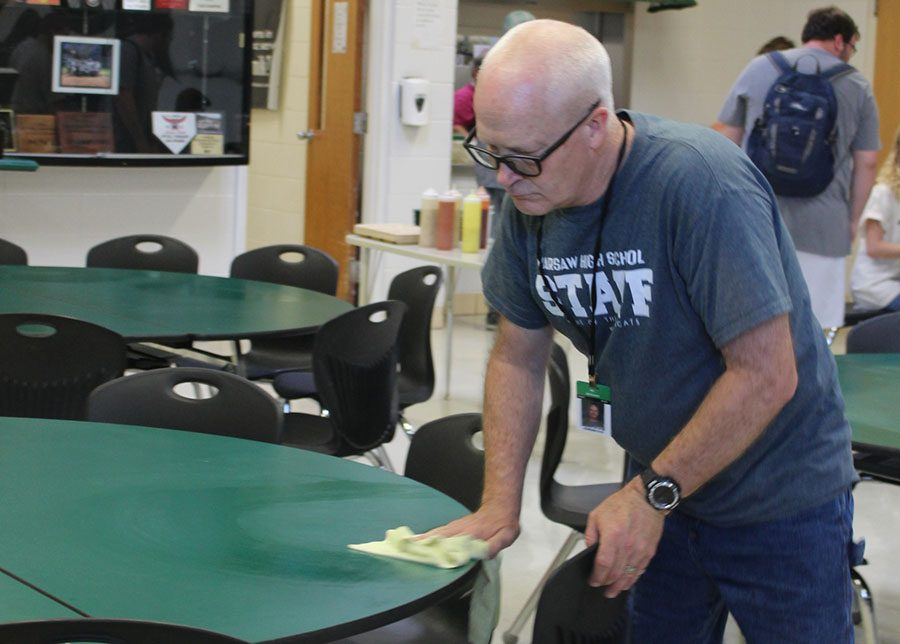 Custodian Steve Johnson wipes down a table in the cafeteria after the first lunch shift. Johnson is beloved among the student body for his positive attitude.