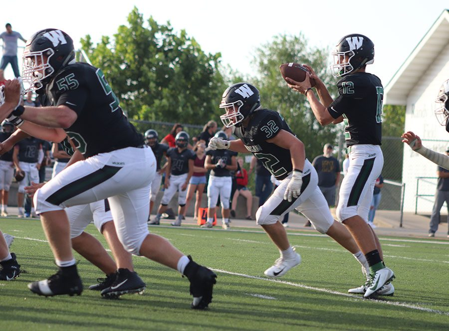 Quarterback Matt Couzens receives the ball at the jamboree on Aug. 23 as Aidan Comer and Zach Chapman provide protection.