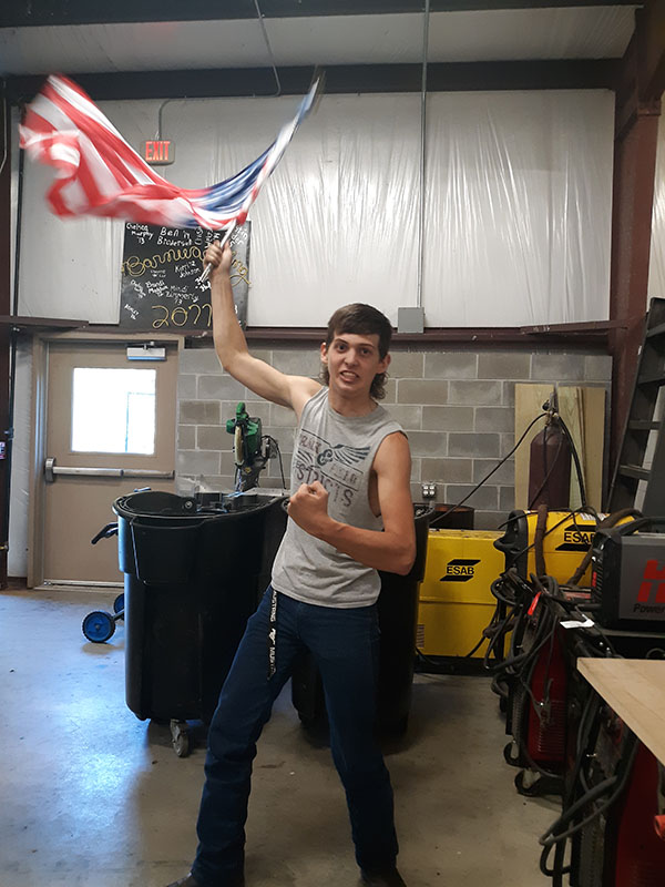 Senior Lerran Yoder waves an American flag to show his patriotism. Yoder claims his mullet is a reflection of his love for this country.