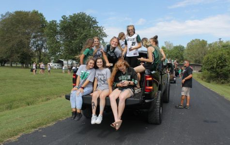 The Warsaw High softball team sits on the back of a truck preparing themselves for the Homecoming parade that took place on Main Street. The softball team rides in the parade every year in hopes to promote and excite the younger students about softball.