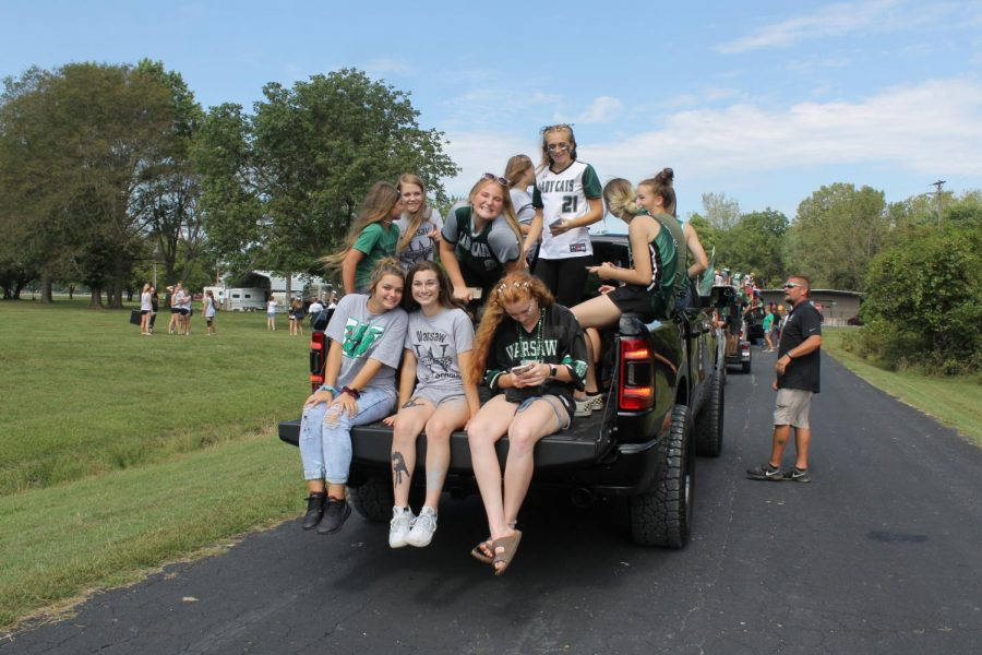 The+Warsaw+High+softball+team+sits+on+the+back+of+a+truck+preparing+themselves+for+the+Homecoming+parade+that+took+place+on+Main+Street.+The+softball+team+rides+in+the+parade+every+year+in+hopes+to+promote+and+excite+the+younger+students+about+softball.+