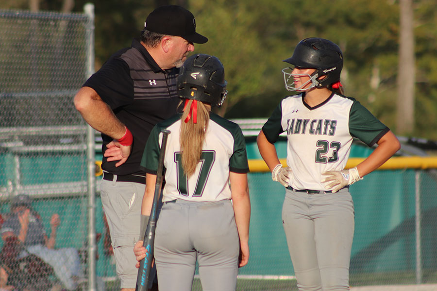 Junior Kylee Fajen and senior Kiersten Grobe talk with their coach Steve Larsen. The team won that night against Marshall on October 2.