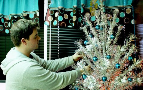 Senior Wade Henderson decorates a Christmas tree in his third hour class. Business teacher Bethany Siegel allowed Henderson to decorate the classroom tree to uplift her Christmas spirit.
